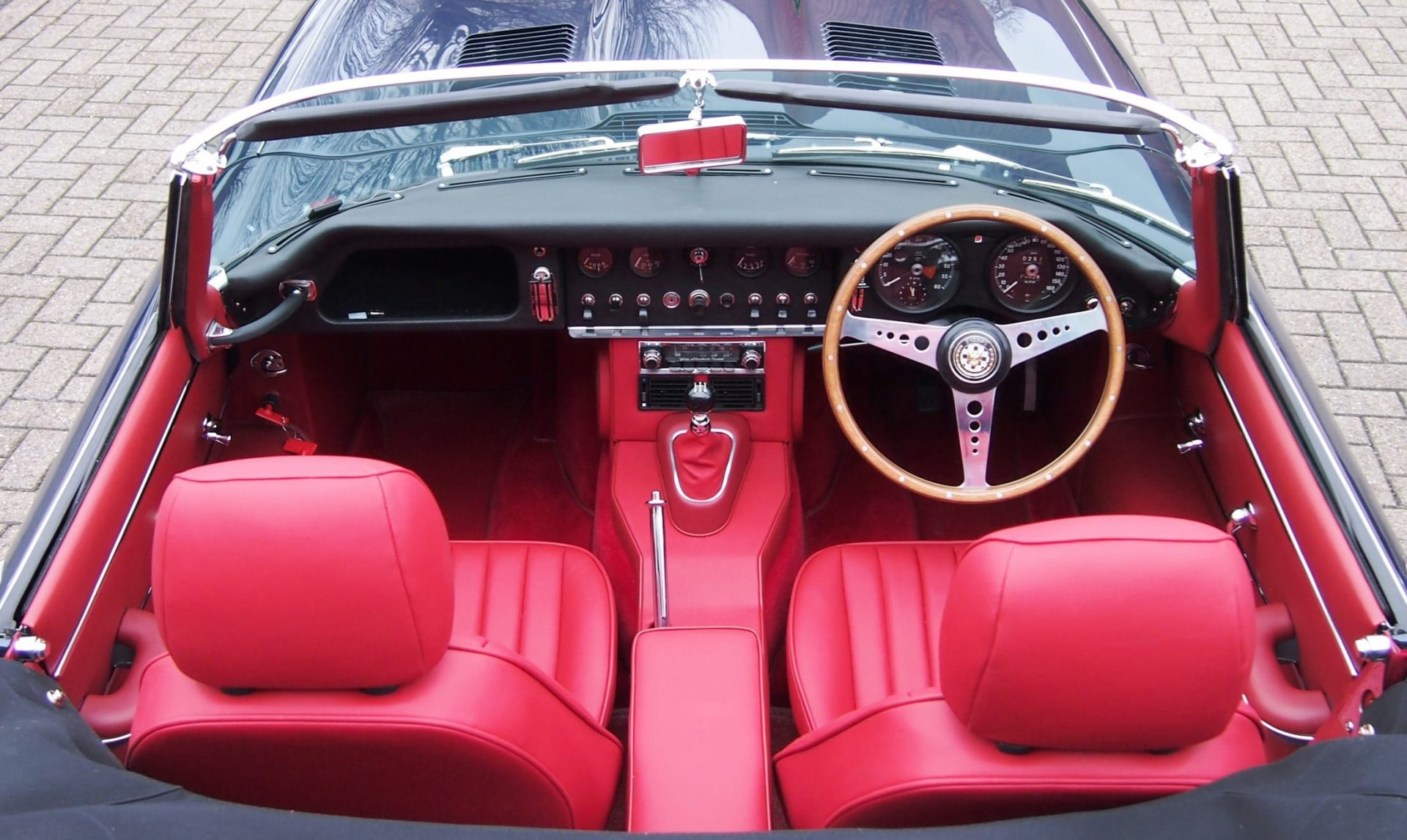 Interior red trim and leather seats inside classic convertible car